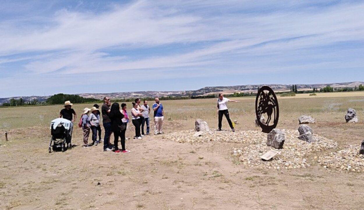 Visitantes junto a una arqueóloga en la necrópolis de Las Ruedas